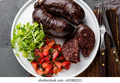 Blood bloody sausages served on white plate with tomato sauce and watercress salad. Gray slate background. Traditional chilean bloody sausage - prieta