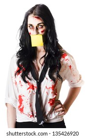 Blood covered businesswoman in zombie makeup with yellow post it note over mouth, white background