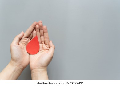 Blood donation - Human hand holding blood drop symbol on gray background with copy space. World blood donor day and save life concept. Flat lay.
