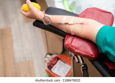 Blood donor at donation with a bouncy ball holding in hand. The hand of a blood donor squeezing a medical rubber ball.