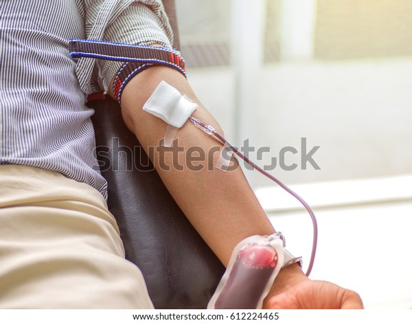 Blood donor at donation, transfusion. Close up right arm of a business man receiving blood in hospital. Healthcare and charity. Also concept image background for World blood donor day - June 14 .