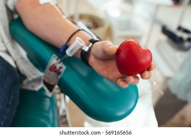 Blood donor squeezes the rubber bulb in the form of heart in his hand