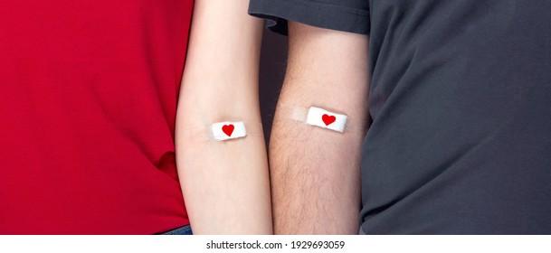 Blutspende. Mann auf Grau und Frau auf rotem T-Shirt mit aufklebtem Pflaster, nachdem Blut mit rotem Herzen gegeben wurde