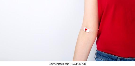 Blutspende. Junge Mädchen in rotem T-Shirt Hand mit Pflaster mit rotem Herzen, nachdem Blut auf grauem Hintergrund. Leerzeichen kopieren