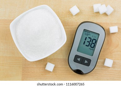 Blood Glucose meter device showing high blood sugar levels, next to bowl of sugar and cubes on wooden background