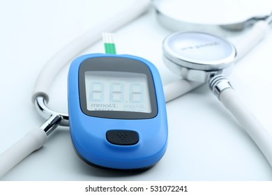 Blood glucose meter and stethoscope on a white background