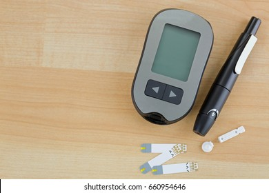 Blood Glucose meter, test strip, lancing pen device on wooden background with copyspace