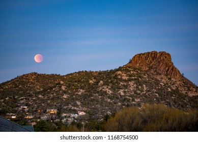 blood moon and Thumb Butte in Prescott Arizona. Moon is orange and sitting next to mountain.