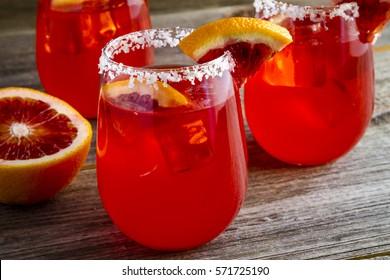 Blood orange margarita cocktails garnished with blood orange slice sitting on rustic wooden table
