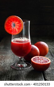 blood oranges and juice of blood oranges on a wooden background, shot with natural light