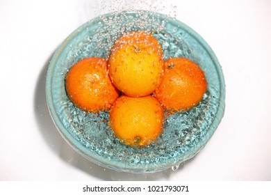 blood oranges on a blue plate with water droplets