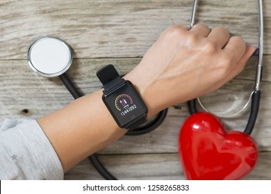 Blood pressure checking or tracking with smart watch and stethoscope on wooden table