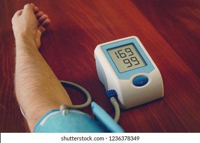 Blood pressure digital pulse monitor. man measuring her blood pressure and hearth rate. Health. hypertension, hypertonia, high blood pressure nourishment. medical examination