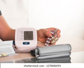 blood pressure measurement with sphygmomanometer. and the person with the blood pressure pill on his hand