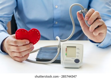 Blood pressure measuring concept. Doctor sitting at the white table and take digital blood pressure monitor and red soft heart in the hands