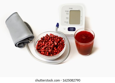 Blood pressure monitor, lingonberry in a transparent dish and lingonberry juice in a glass. The concept of utility lingonberries for the cardiovascular system and blood pressure
