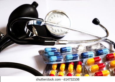 a blood pressure monitor and medicines in different colored capsules on white background