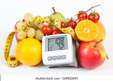 Blood pressure monitor with result of measurement, fresh fruits with vegetables and tape measure, healthy lifestyle, slimming and prevention of hypertension concept