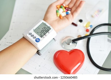 Blood pressure monitoring of  hypertensive patient holding pharmaceutical pill above electrocardiogram paper
