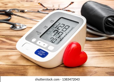 Blood pressure tonometer with red heart on wooden table. Medical concept.