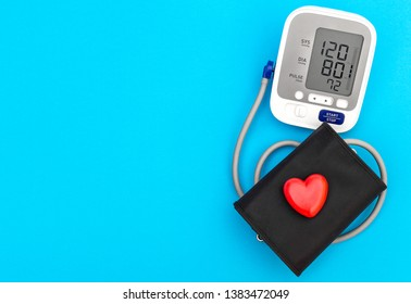 Blood pressure tonometer with red heart on blue background. Medical concept. Top view. Space for text.