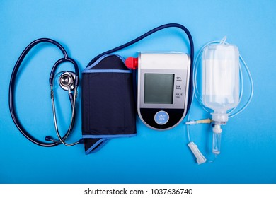 Blood presure mesurement tool next to a stethoscope and other medical devices on blue background