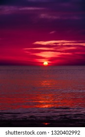 Blood red and dark purple sunset of sun sets over horizon Adaman Sea
