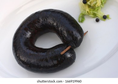 Blood sausage or black pudding, made with pig's blood and buckwheat kasha or rice, served with  cooked cabbage and juniper berries