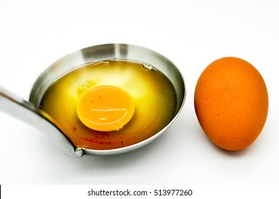 Blood spots in egg, a raw egg in the ladle in white background