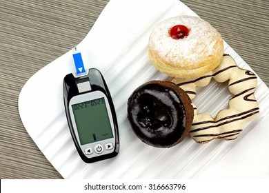 Blood sugar measurement, Diabetic kit, Blood glucose meter test kit. Unhealthy food like donut and confectionery increase sugar in blood.