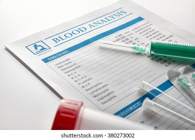 Blood test report with vials, urine container and syringe over white glass table. Horizontal composition. Elevated view.