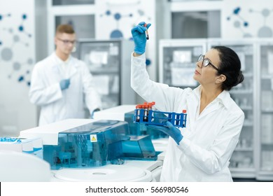 Blood test tubes. Senior female scientist examining blood test tubes at her laboratory dna testing analysis profession specialist clinician experienced medicine healthcare doctor concept copyspace