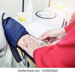 With the blood-pressure cuff still in place, a nurse, phlebotomist, or technician tapes the hypodermic to collect the blood to the donor's arm.