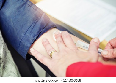 With the blood-pressure cuff still in position round the donor's arm, a technician uses a needle to start withdrawing blood from a vein.
