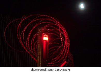 The blood-red razor wire isolated on the black night background