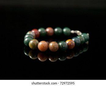 Bloodstone bracelet with black background and reflection