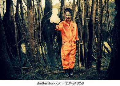 Bloodthirsty clown man in a night forest with a candy-floss. Halloween. Horror.