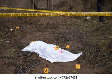 Bloody body cover in the middle of the forest with evidence markers and crime scene track.