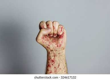 bloody and dirty left fist raising up in front of grey background