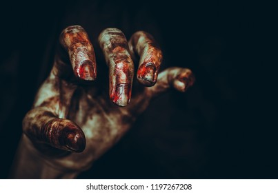 Bloody dirty zombie hand on black background with copy space. Halloween spooky poster