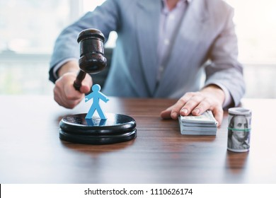 Bloody game. Greedy wicked official touching money and touching an inscribed gavel
