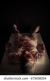 Bloody gauze covered young mummy in darkness displayed on light colored table