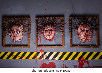 Bloody ghastly skins from human heads stuck in square frames above yellow and black warning symbol