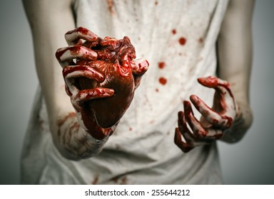 Bloody Halloween theme: crazy killer keeps bloody hands torn bloody human heart and experiencing depression and pain
