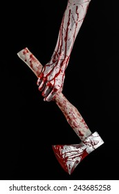 Bloody Halloween theme: bloody hand holding a bloody butcher's ax isolated on black background in studio