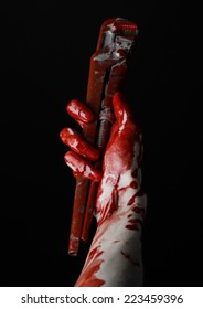 bloody hand holding an adjustable wrench, bloody key, crazy plumber, bloody theme, halloween theme, black background,isolated, bloody hand of an assassin, bloody murderer, psycho, bloody monkey wrench