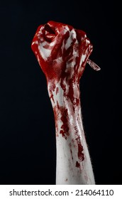 Bloody hand with a scalpel, a nail, black background, zombie, demon, maniac