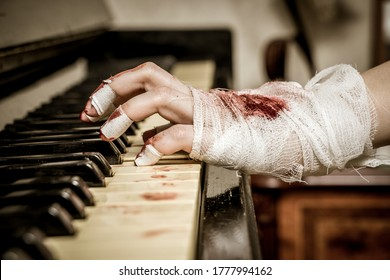 Bloody hands in bandages play the piano