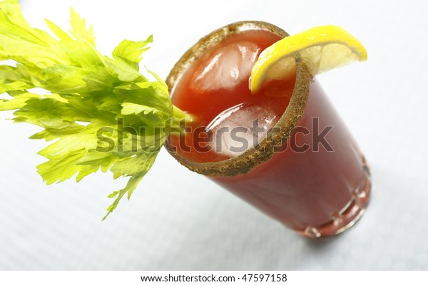bloody or mary caesar drink with celery and ice cube. Shallow depth of field.