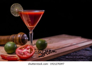 Bloody Mary cocktail decorate with  tomato, lime , chili , black pepper, paprika powder and pepper mill on wood in black background